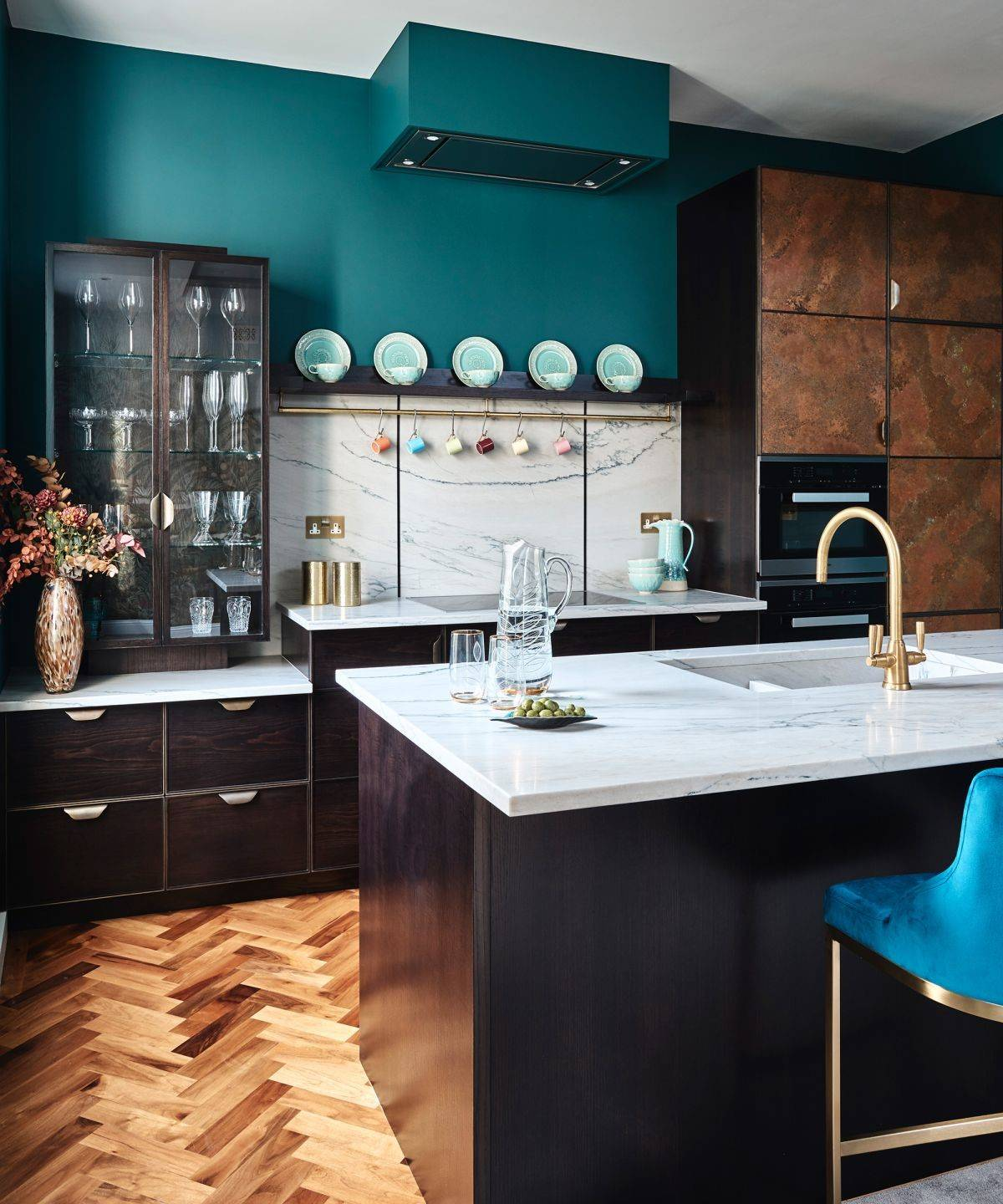 green kitchen paint against dark wood cabinets and marble countertops