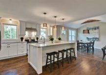 white panelled kitchen island with black stools