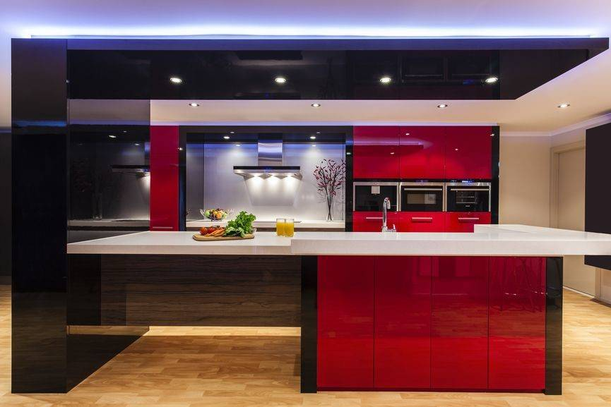 modern kitchen with low lighting and bright red cabinets
