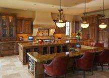 dark wood panelled kitchen with luxurious arm chairs at island