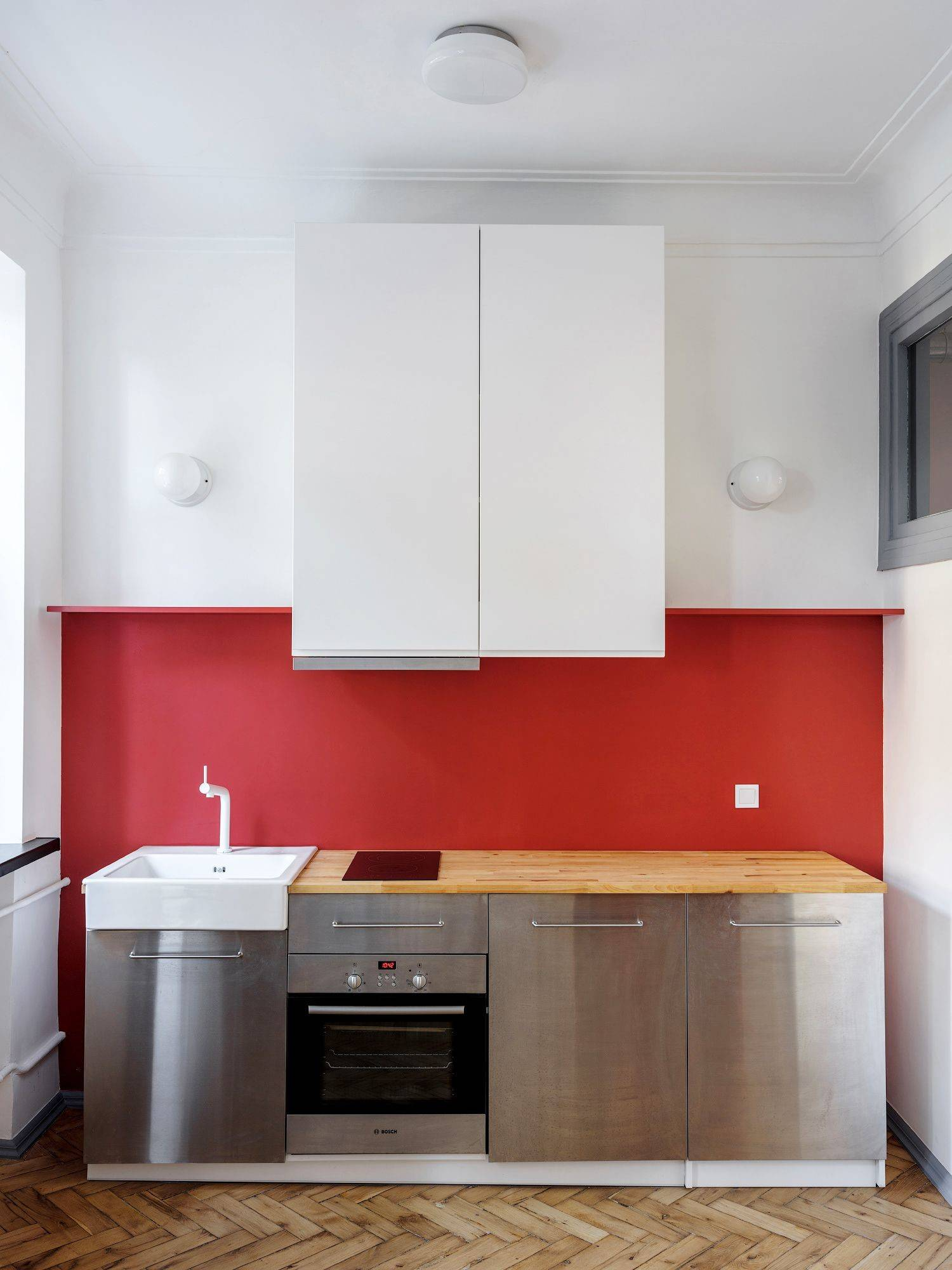 red wall in kitchen with stainless steel appliances and white cabinets