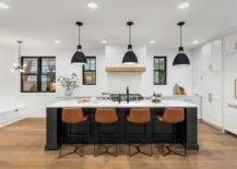 black kitchen island with white countertop and orange stools