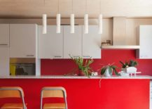 bright red kitchen island with white upper cabinets and hanging candle lights