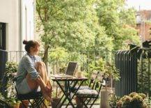 woman seated at table on balcony with container garden