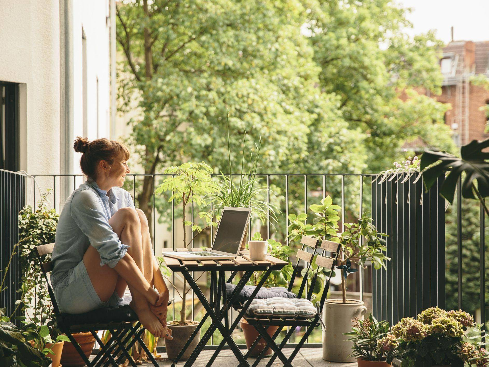 woman seated at patio table on balcony