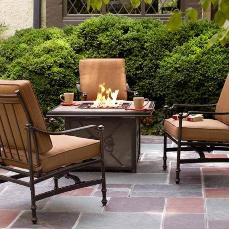lit firepit with beige chairs surrounding on patio