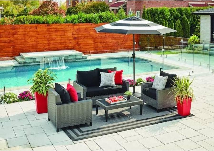 striped umbrella covering dark patio furniture