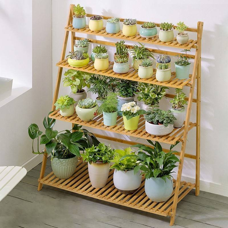 bamboo hanging plant stand with rows of succulents and plants