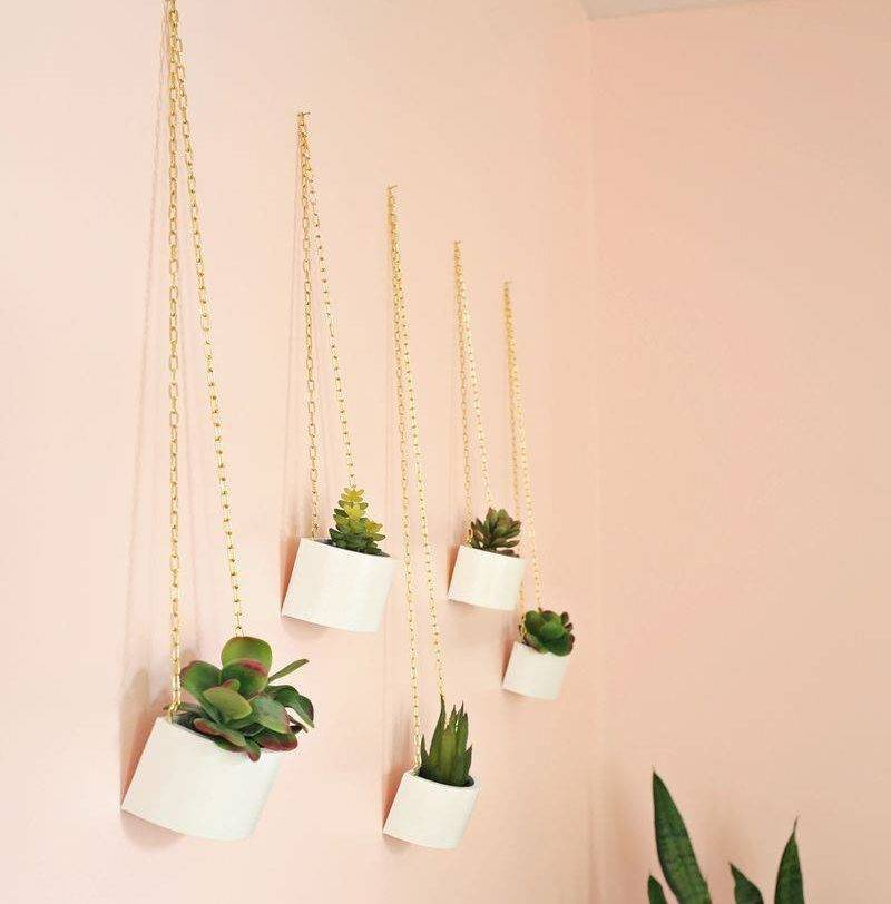 wooden planters hanging on peach wall