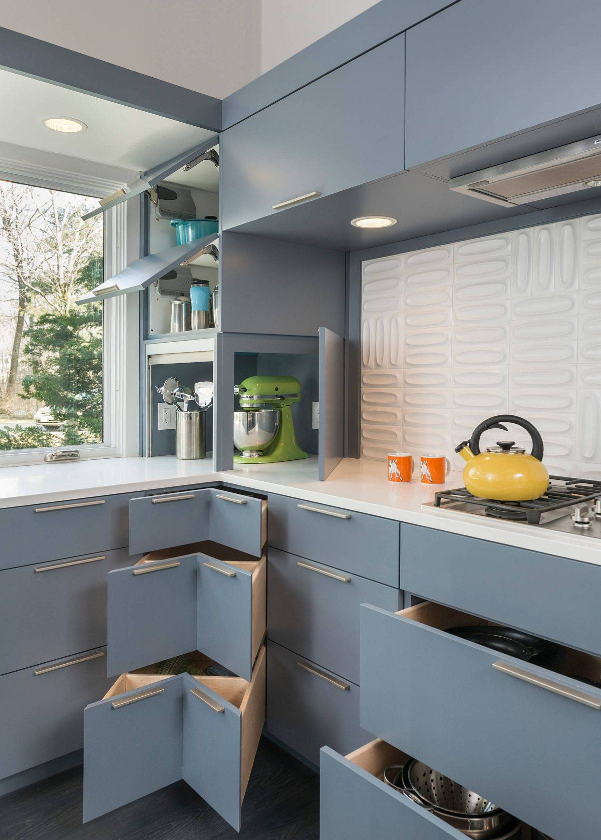 Gray corner cabinets and custom units offer a variety of delightful storage options in this kitchen