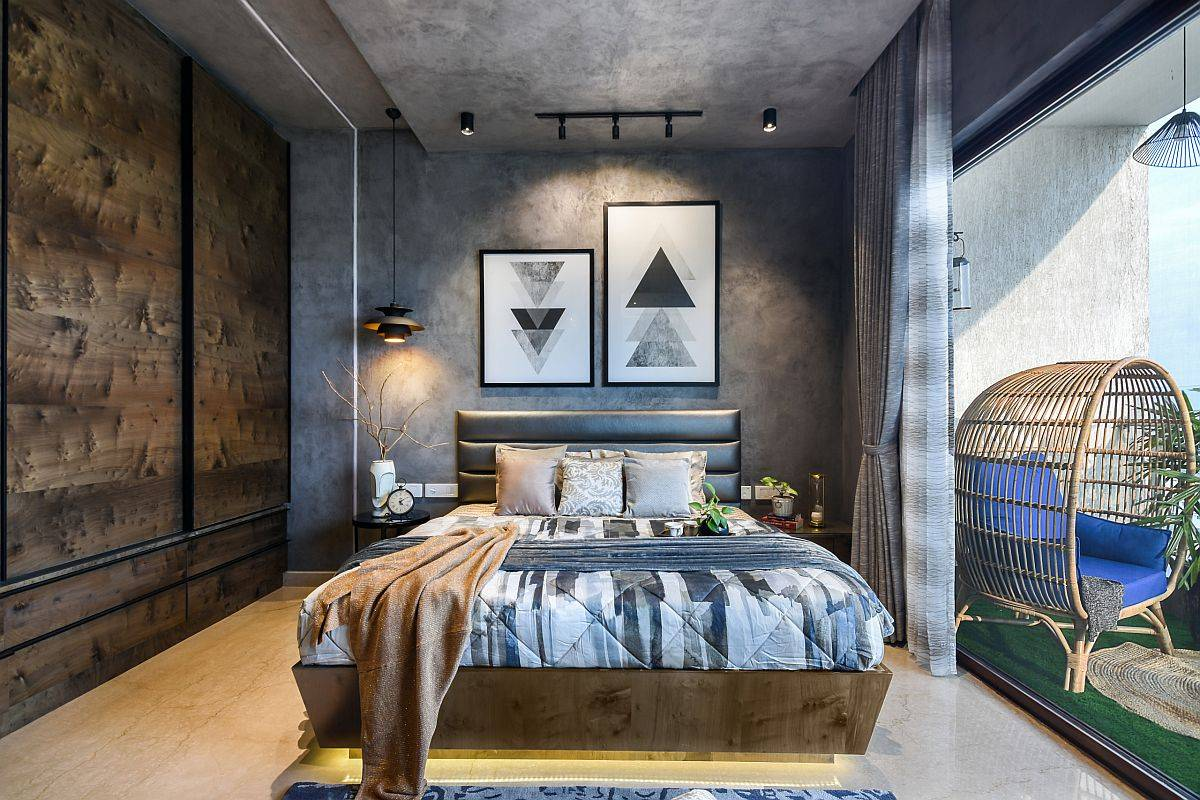 Raw cement backdrop in the bedroom adds an edgy vibe to the contemporary theme of this bachelor bedroom