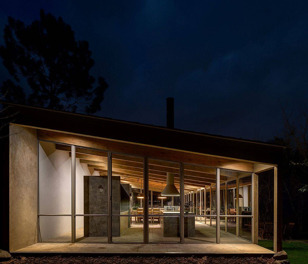 Sloped ceiling of the home is even more prominent after sunset thanks to warm lighting