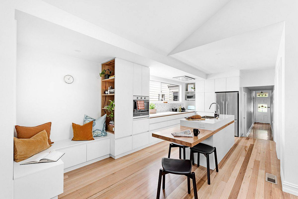 Smart-and-modern-extension-of-the-kitchen-island-is-a-wooden-breakfast-bar-that-brings-visual-contrast-to-the-space-70539