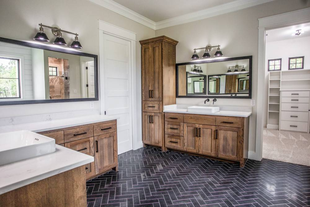 Spacious farmhouse style bathroom in white and wood with dark tiled floor in herringbone pattern