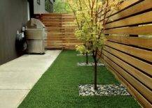 backyard pallet fence surrounding faux grass and barbecue