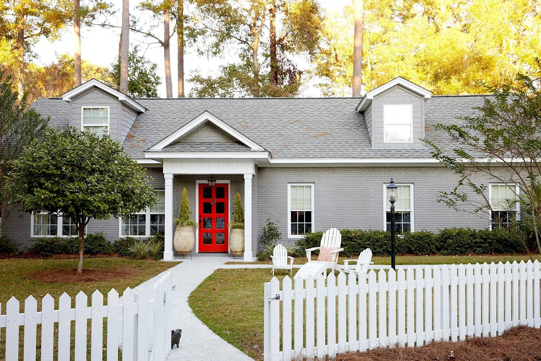 white picket fence in front of grey home with red door