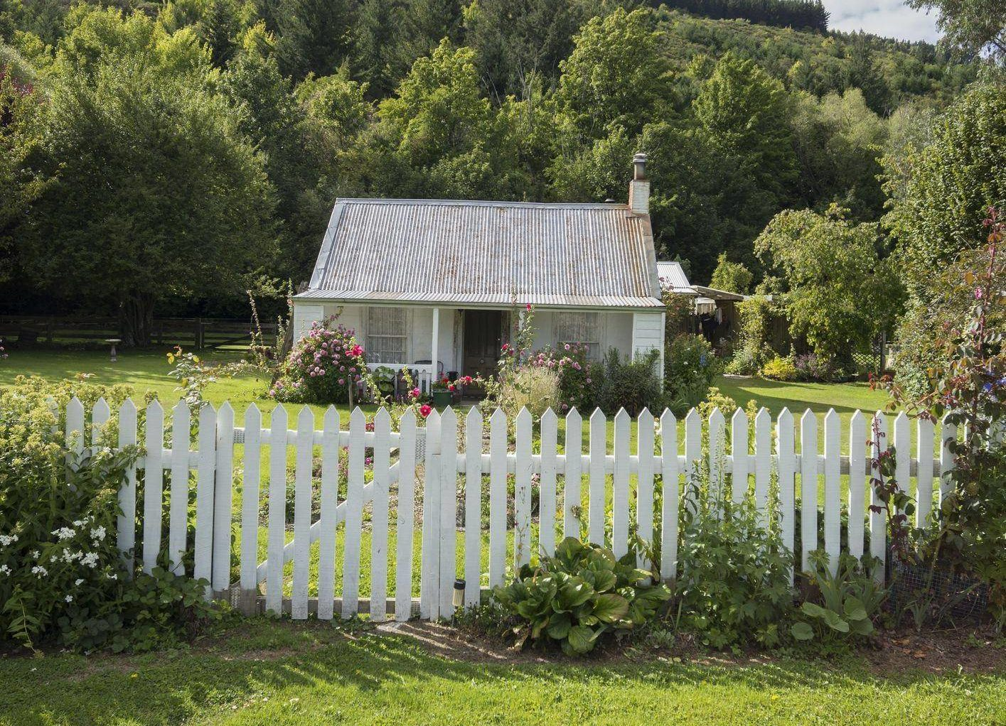 white picket fence in front of cottage
