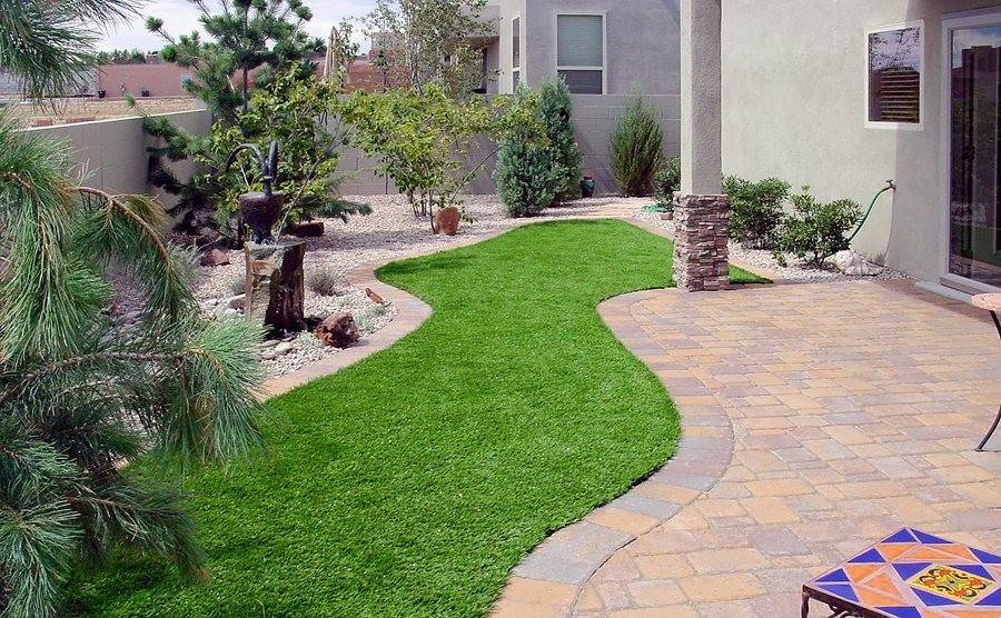 faux grass patch in between patio sections of backyard