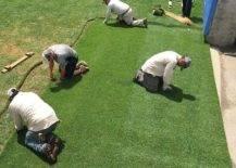 men laying down sod