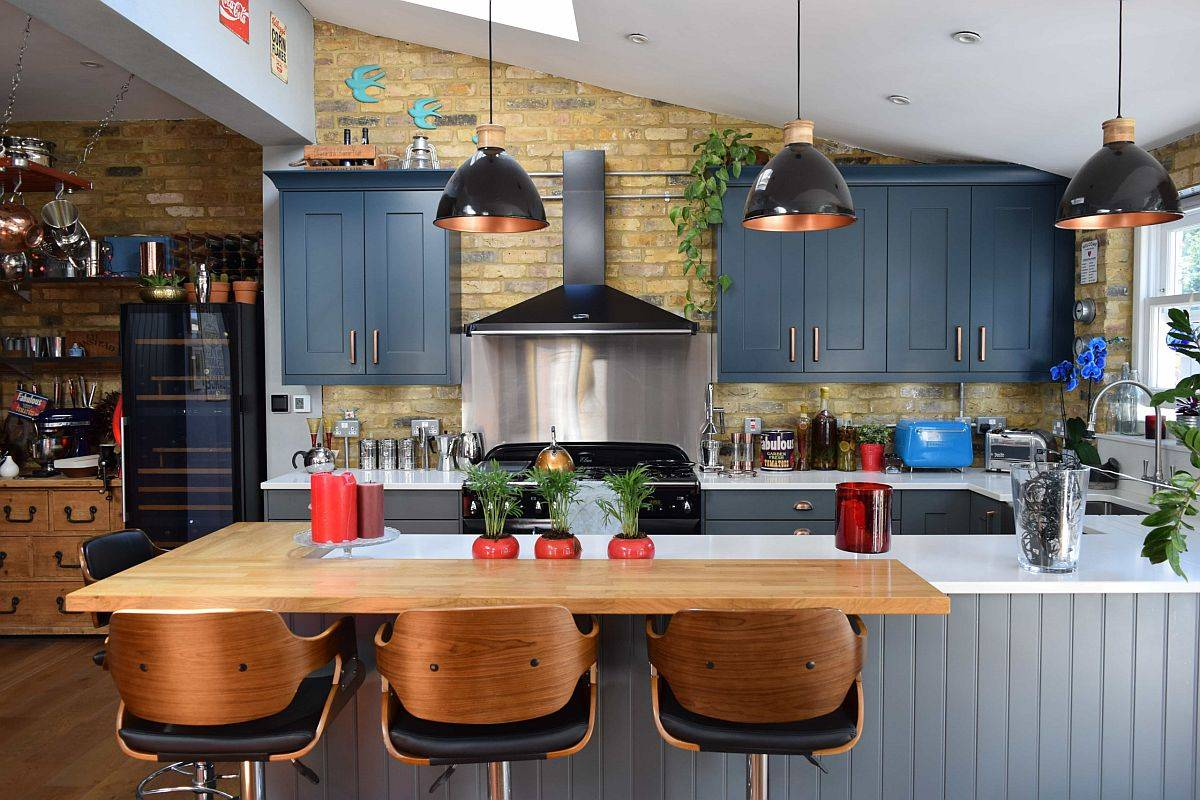 Captivating modern farmhouse kitchen with an L-shaped wooden breakfast bar, deep blue cabinets and ample textural contrast