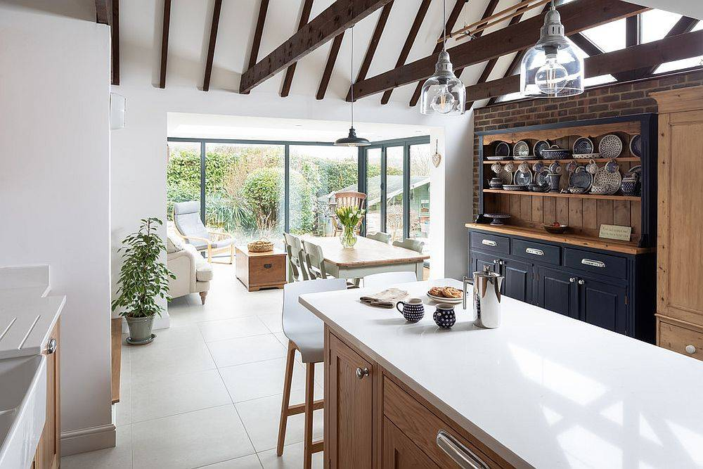 Charming little kitchen connected with the backyard embraces white and gray along with exposed wood ceiling beams and brick wall section
