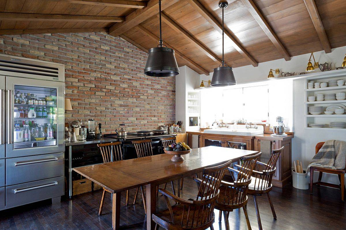 Dashing-industrial-farmhouse-eat-in-kitchen-with-a-brick-wall-and-large-wooden-table-at-its-heart-83925