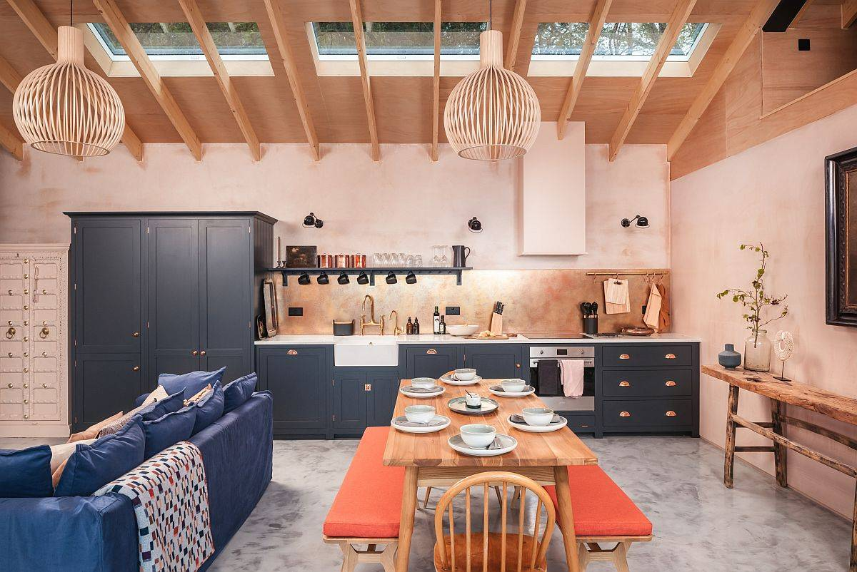 Eye-catching-Scandinavian-style-kitchen-with-light-pink-walls-brings-orange-to-the-setting-using-twin-benches-at-the-dining-table-74313