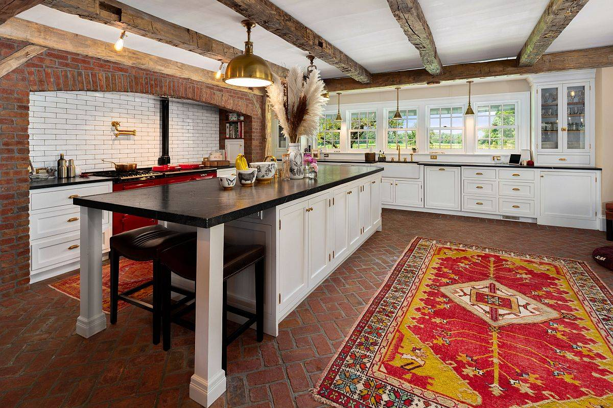 It is the rug that adds a bright pop of color to this spacious kitchen with brick walls and floor