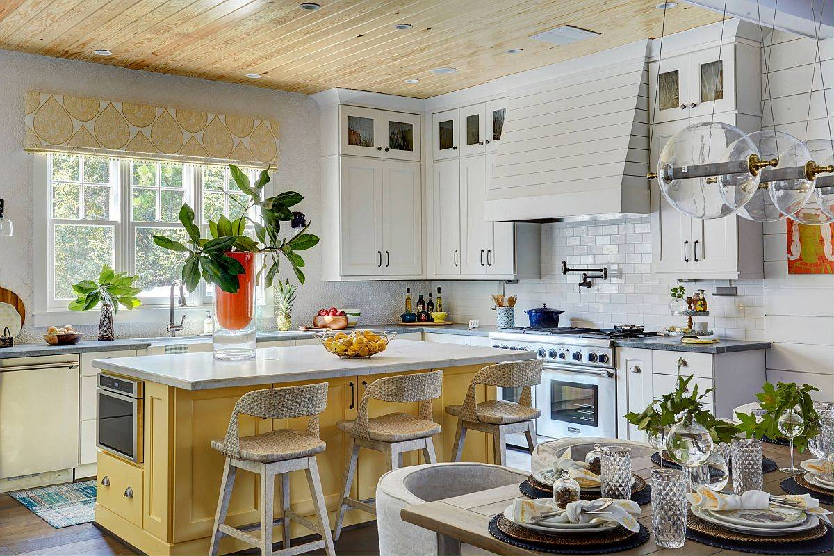 Picture-perfect modern farmhouse kitchen with a colorful yellow kitchen and woodsy ceiling