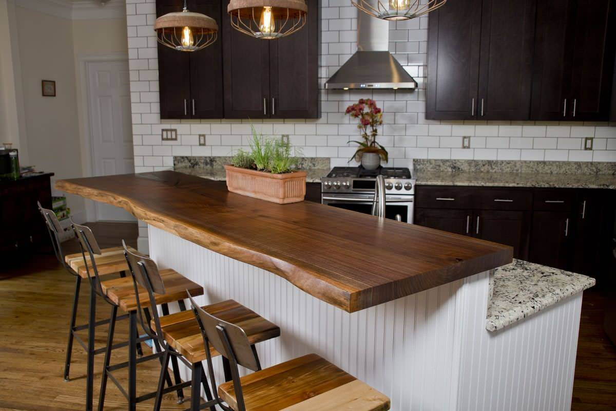 Polished-black-walnut-tree-countertop-serves-as-the-breakfast-bar-in-this-small-industrial-kitchen-with-a-convenient-island-98180