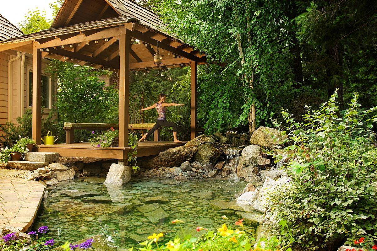 Rustic deck surrounded by greenery and a water feature is the perfect place for your yoga sessions