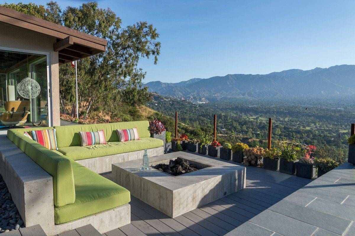 Slate tile and concrete along with a fire pit shape this fabulous outdoor sitting area with captivating view
