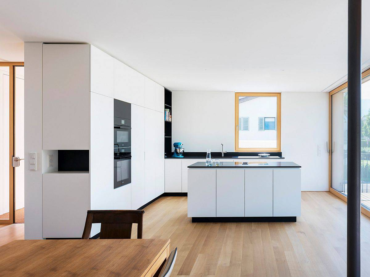 Sleek-contemporary-kitchen-in-white-with-wooden-floors-and-appliances-in-black-69116