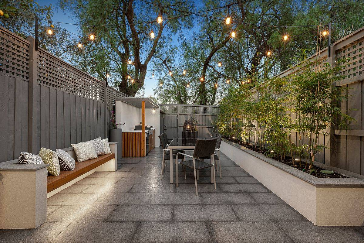 Smart and polished contemporary patio with a lovely built-in bench, string lights and greenery