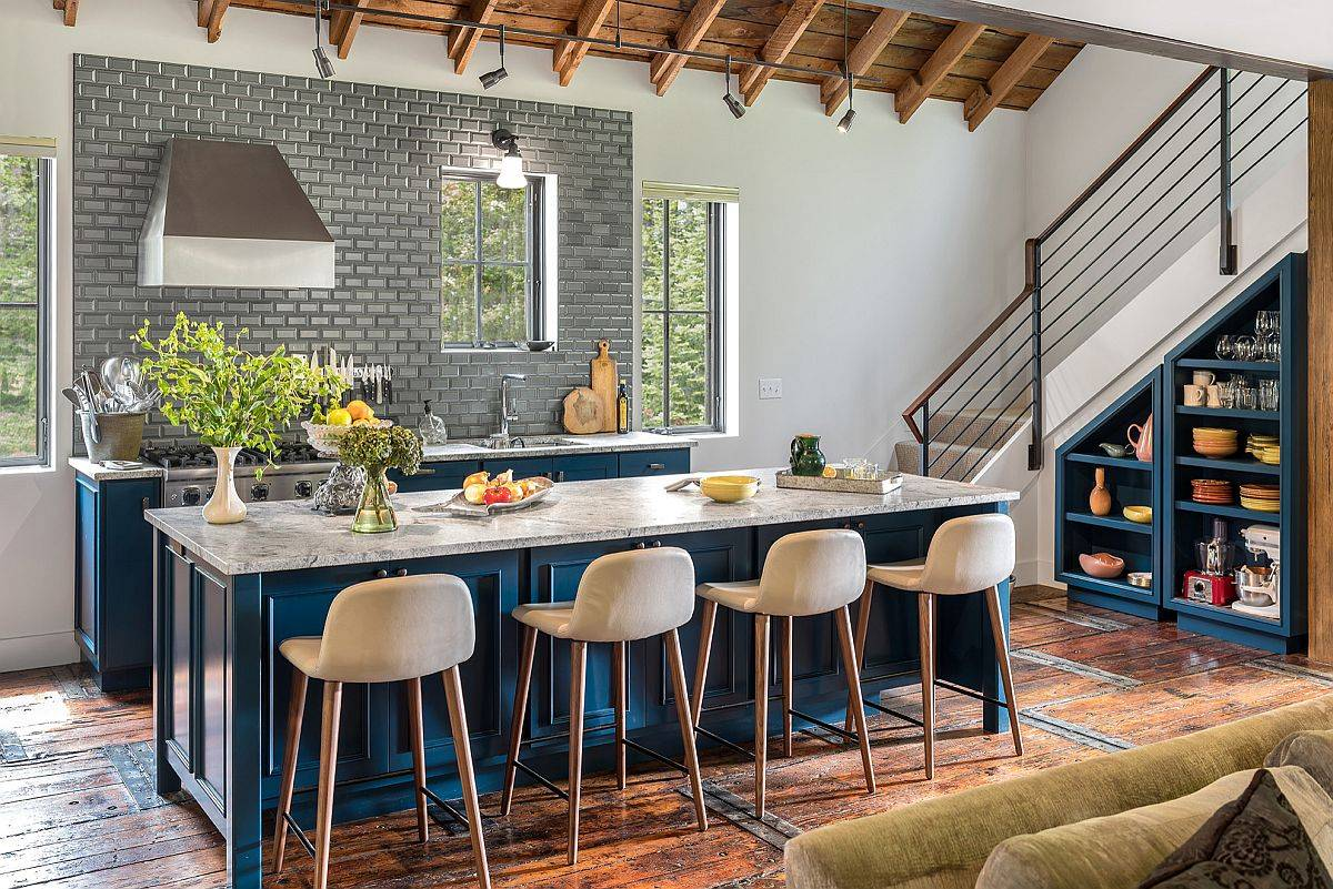 Stone countertops, bright blue island and a backsplash in gray balance modern and farmhouse elements in this kitchen