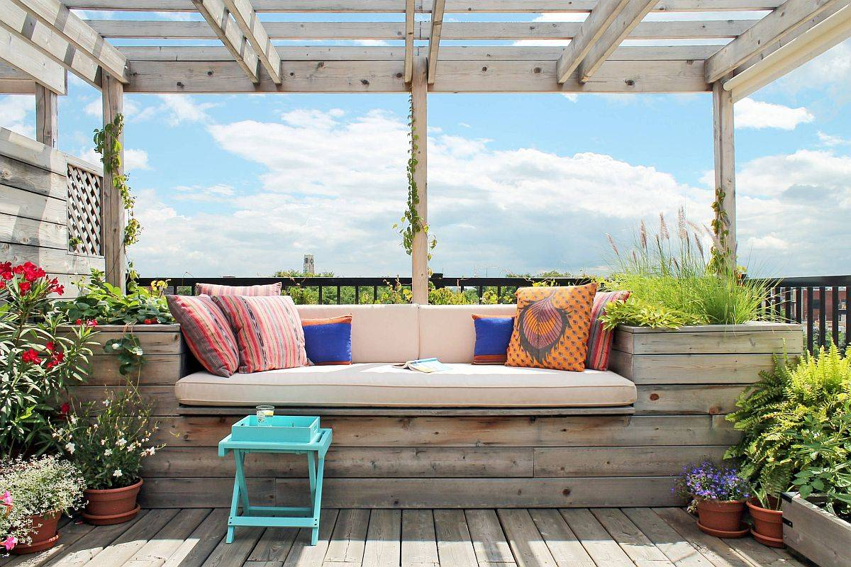 Wooden built-in bench, pergola and deck along with lovely plants create an urban green refug