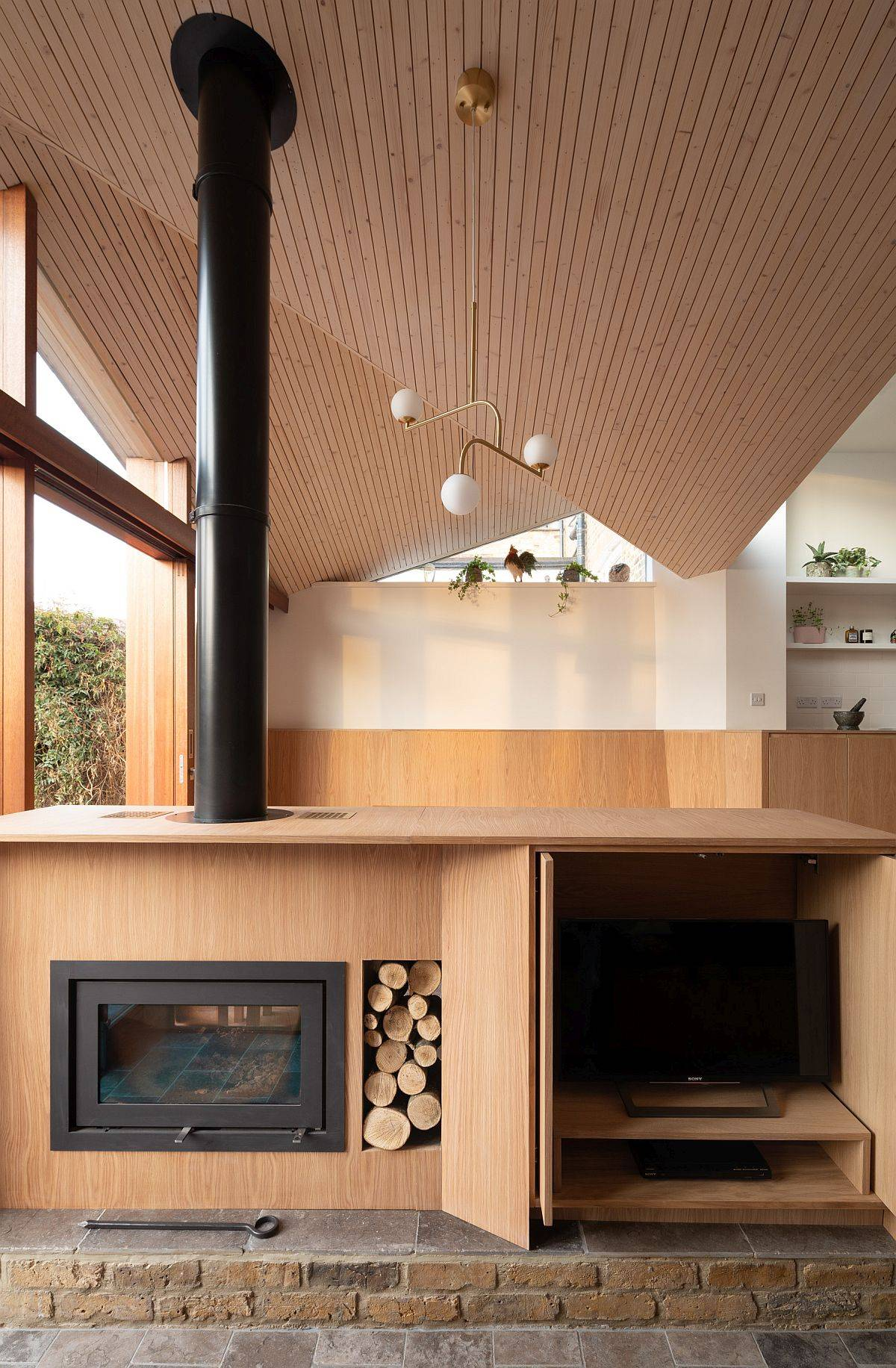 Wooden-cabinet-next-to-the-fireplace-opens-up-to-reveal-the-TV-10163