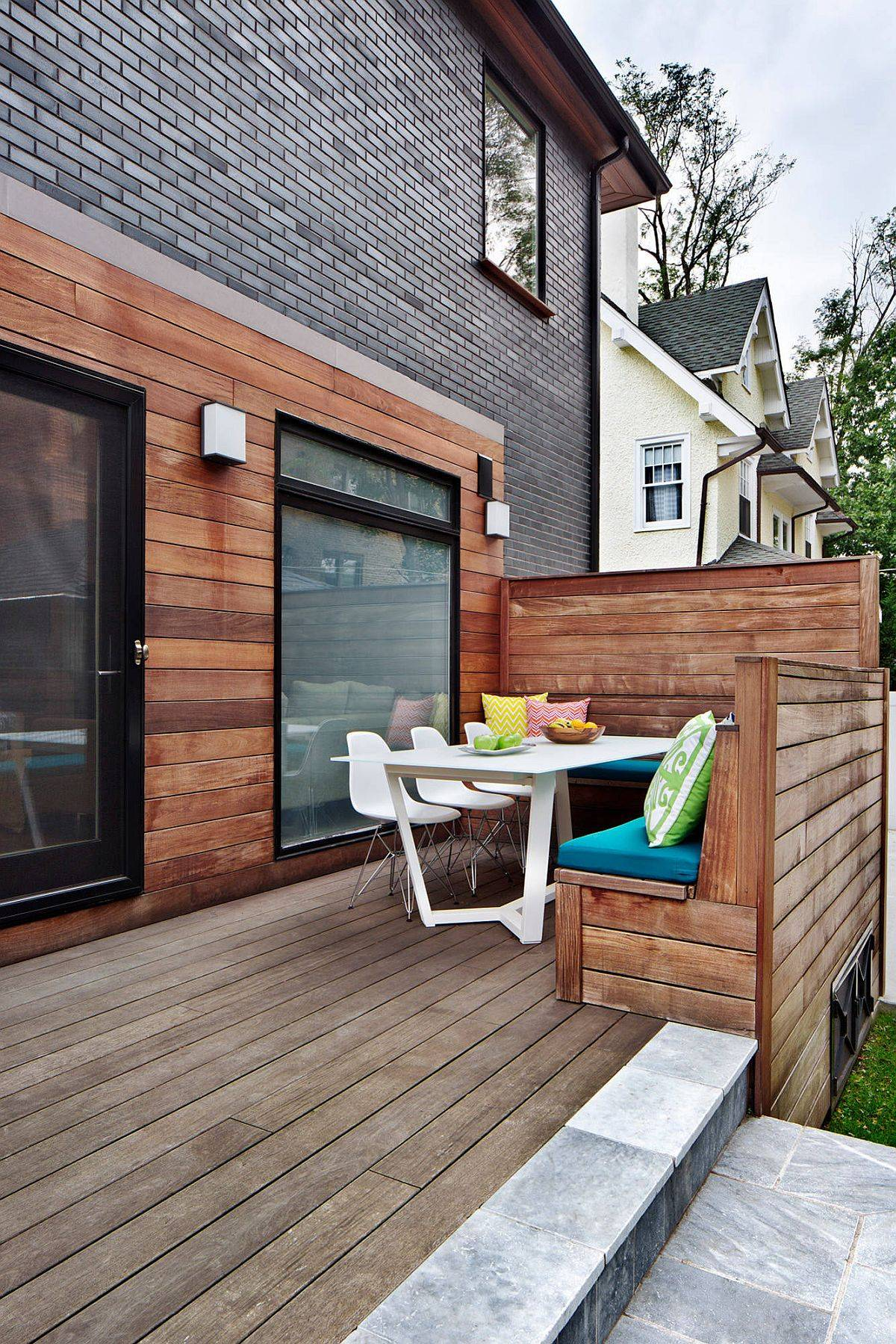 colorful pillows and cushions add cheerful charm to the wooden built-in bench on the patio