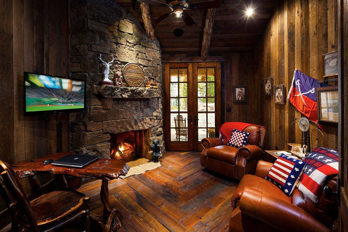 Gorgeous mountain cabin-inspired small rustic home office with stone walls. fireplace, live-edge desk and comfy seating